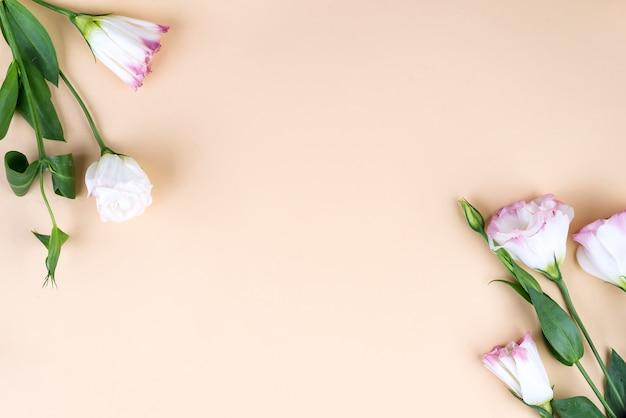 Feld zusammensetzung mit dem leeren raum in der mitte, die von blühendem rosa eustoma, ebenenlage gemacht wird. dekorative mit blumenecken auf beige hintergrund. Premium Fotos