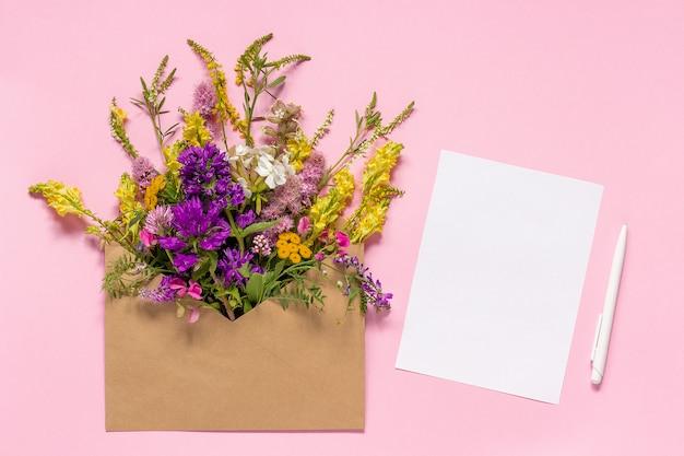 Feldblumen im handwerksumschlag und in der weißen leeren papierkarte Premium Fotos