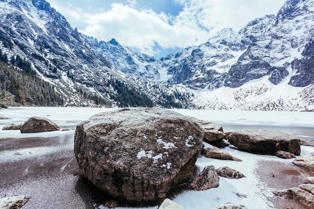 Felsen über dem see mit bergen im winter Kostenlose Fotos