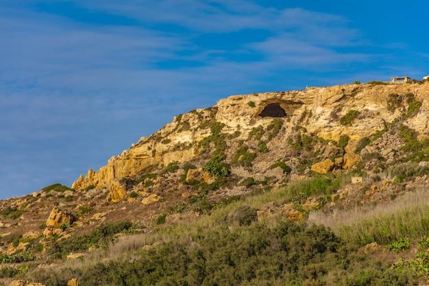 Felsiger hügel mit vielen grünen pflanzen unter dem schönen klaren blauen himmel Kostenlose Fotos