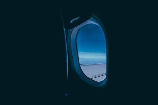 Fenster des flugzeugs mit blick auf den flügel und den blauen himmel Kostenlose Fotos