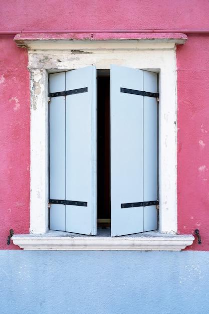 Fenster mit blauem fensterladen auf rosa wand. Premium Fotos