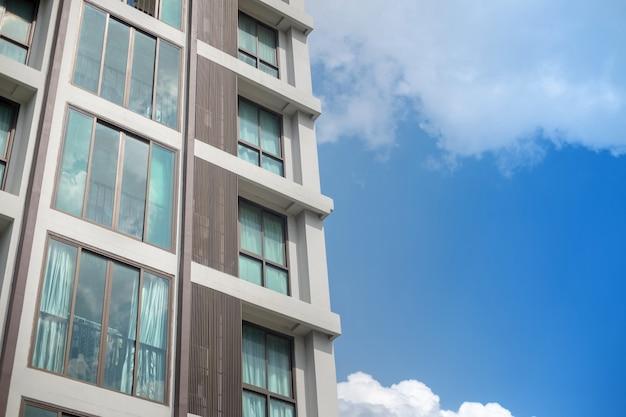 Fenstergitter des modernen kondominiumgebäudes mit hintergrund des blauen himmels der weißen wolke Premium Fotos