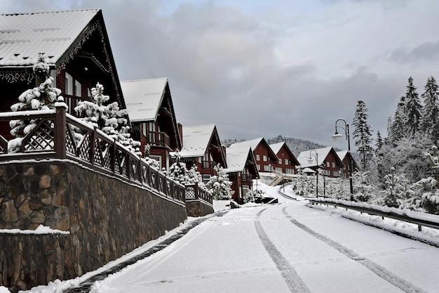 Ferienhaus aus holzhütten im ferienort in den bergen, bedeckt mit frischem schnee im winter. schöne winterstraße nach schneefall. Premium Fotos