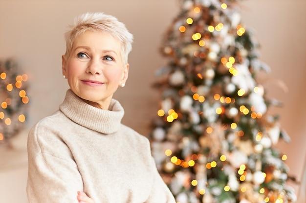 Ferienzeit, tradition und feierkonzept. attraktive sechzigjährige frau im kuscheligen pullover, der im wohnzimmer steht, verziert mit majestätischem weihnachtsbaum mit ornamenten, girlanden und lichtern Kostenlose Fotos
