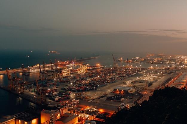 Fernaufnahme eines hafens mit booten, die nachts mit fracht und versand beladen sind Kostenlose Fotos