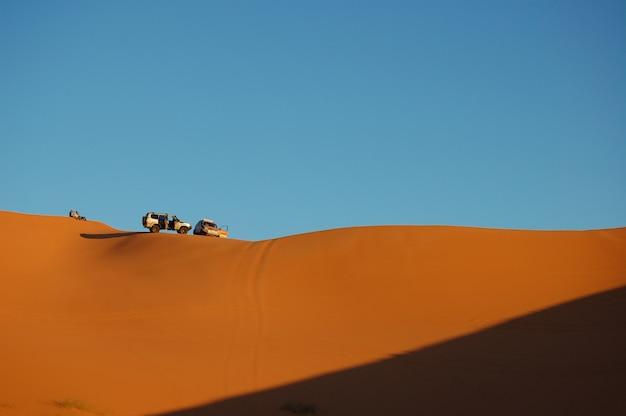 Fernschuss von zwei autos, die an einem sonnigen tag auf den sanddünen mit klarem blauem himmel geparkt sind Kostenlose Fotos