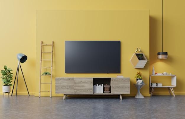 Fernsehapparat auf kabinett im modernen wohnzimmer mit lampe, tabelle, blume und anlage auf gelber wand. Premium Fotos