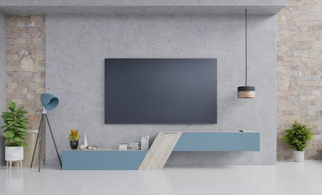 Fernsehen auf blauem kabinettdesign im modernen wohnzimmer mit lampe, blume und anlage auf zementwand. Premium Fotos
