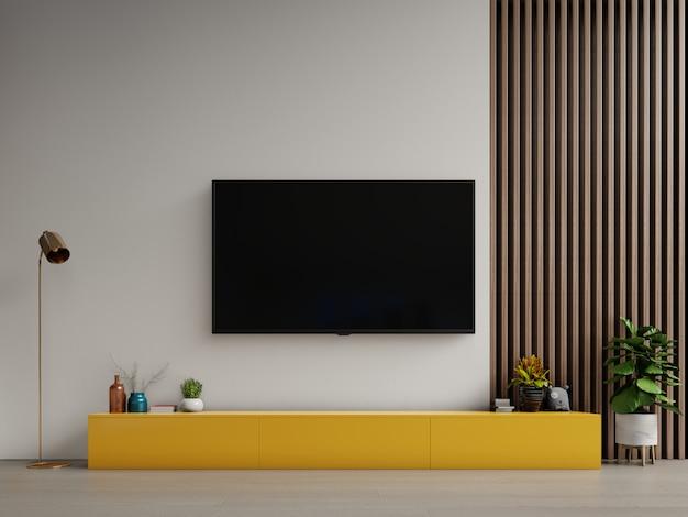 Fernsehen auf gelbem kabinett oder platzgegenstand im modernen wohnzimmer mit lampe, tabelle, blume und anlage auf weißem wandhintergrund. Premium Fotos