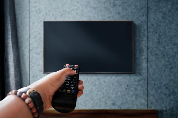 Fernsehen konzept beobachten. hand, die fernsehfernbedienung hält, um kanal zu steuern oder zu ändern Premium Fotos