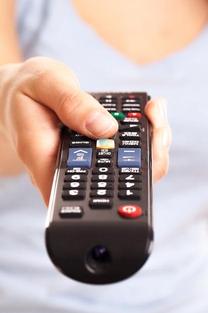 Fernsehkonsole in der hand der frau Kostenlose Fotos