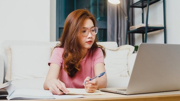 Fernunterrichtsstunde der jungen asiatischen teenager-studentin mit online-lehrer und studie auf computer-laptop im wohnzimmer von zu hause in der nacht. soziale distanzierung, quarantäne zur vorbeugung von koronaviren. Kostenlose Fotos
