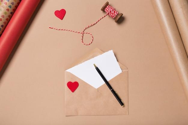Fertigen sie umschlag mit rotem herzen, leerem papier und stift auf beige tabelle an. verpackung. liebe konzept. valentinstag Premium Fotos