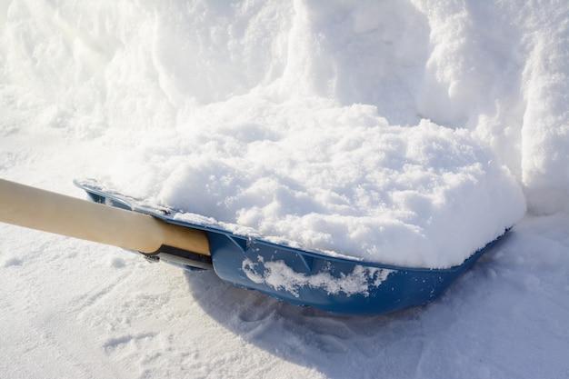Fertigschaufeln des schnees in der plasterung. schneeschaufel nahe einem großen snowbank beim säubern Premium Fotos