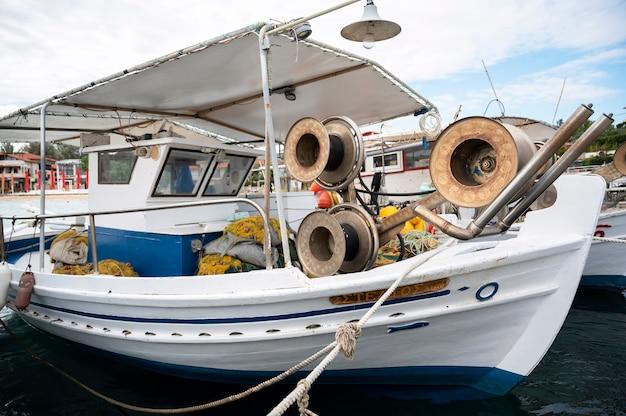 Festgemachtes boot mit vielen angelzubehörteilen im seehafen, ägäisches meer in ormos panagias, griechenland Kostenlose Fotos