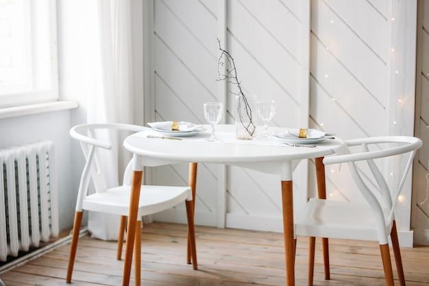 Festlich gedeckter tisch für zwei, minimalistische weihnachtsdekoration. skandinavisches interieur Premium Fotos
