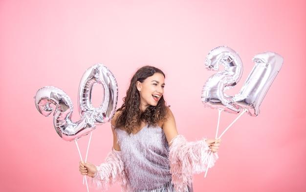Festlich gekleidetes junges mädchen, das auf einem rosa hintergrund mit silbernen weihnachtsballons für das neujahrskonzept lacht Kostenlose Fotos