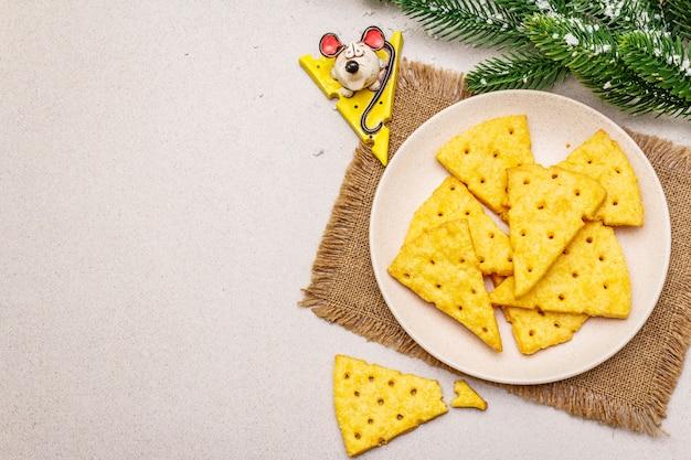 Festliche käsecracker, snackkonzept des neuen jahres. plätzchen, mäusefigur, tannenbaumast, künstlicher schnee, sackleinen-serviette. Premium Fotos