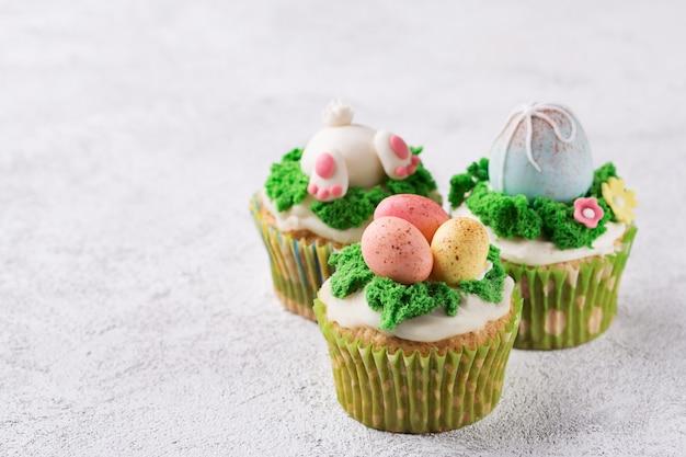 Festliche kleine kuchen mit mastixeiern und gras auf hellem hintergrund. ostern-feiertagskonzept. kopieren sie platz Premium Fotos