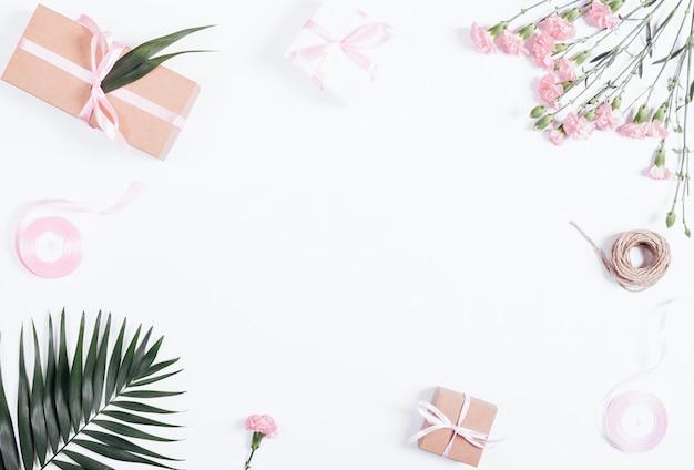 Festliche komposition: schachteln mit geschenken, bändern und blumen auf weißem tisch Premium Fotos