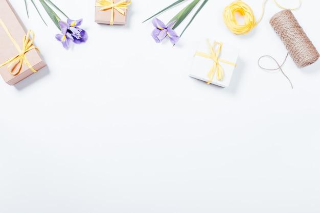 Festliche zusammensetzung auf weißem hintergrund: blumen, kästen mit geschenken, bänder Premium Fotos