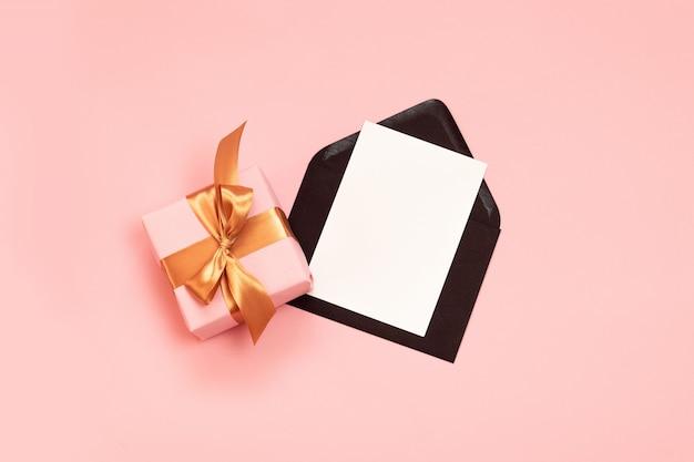 Festliche zusammensetzung der draufsicht mit dem schönen geschenk eingewickelt im feiertagspapier, gold ribbonnd schwarzer umschlag mit papierschablone auf rosa Premium Fotos