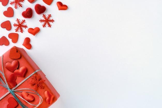 Festliche zusammensetzung von gebundener roter geschenkbox, schneeflocken und herzen zerstreute auf weiß für valentinstag Premium Fotos