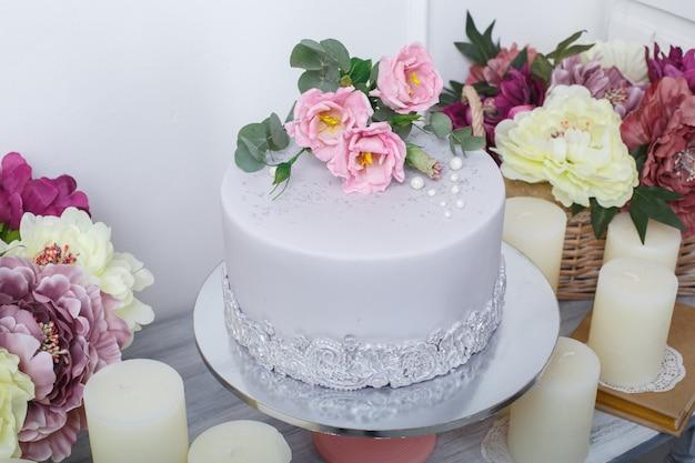 Festlicher kuchen mit mastix wird mit rosa blumen nah oben verziert. schöne leckere torte decoratrd mit rosen am geburtstag oder hochzeitsfeier. schokoriegel auf dem festlichen tisch. Premium Fotos