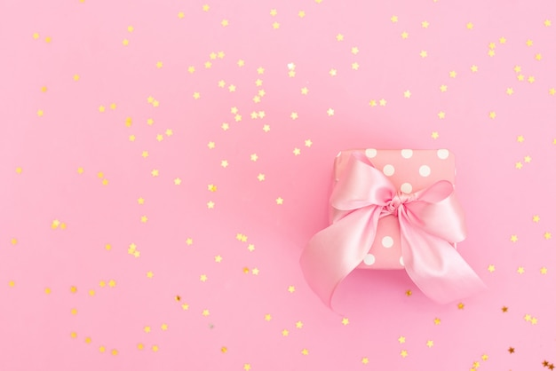 Festlicher rosa hintergrund. geschenk mit satinbogen und glänzenden sternen auf hellrosa pastellhintergrund. Premium Fotos