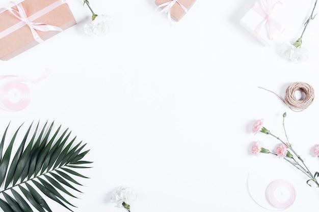 Festliches arrangement: schachteln mit geschenken, bändern und blumen auf weißem tisch Premium Fotos