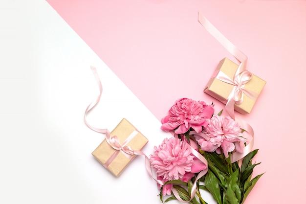 Festliches konzept von pfingstrosen und von geschenken auf weiß und rosa Premium Fotos