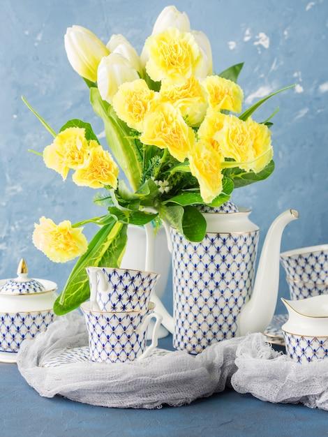 Festliches set der ostern-teeparty und gelbe blumen Premium Fotos