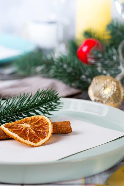 Festliches weihnachts- und des neuen jahresdetailsgedeck mit trockener orange und zimt auf einem grauen gewebe. essplatz eingerichtet Premium Fotos