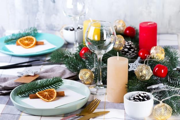 Festliches weihnachts- und neujahrsgedeck mit trockener orange und zimt auf einem grauen gewebe. essplatz mit tannenzapfen, zweigen und kerzen dekoriert Premium Fotos