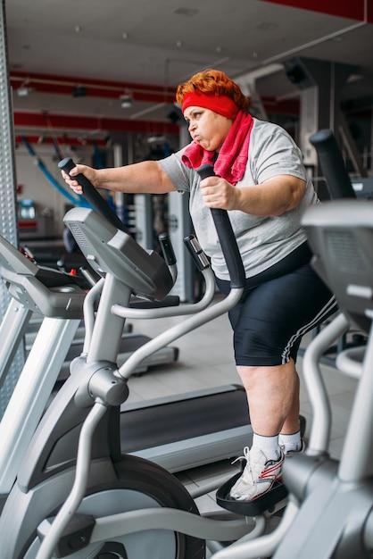 Fette frau, die übungsmaschine für gehen, training im fitnessstudio verwendet. kalorien brennen, fettleibige weibliche person im sportverein, dicke leute Premium Fotos