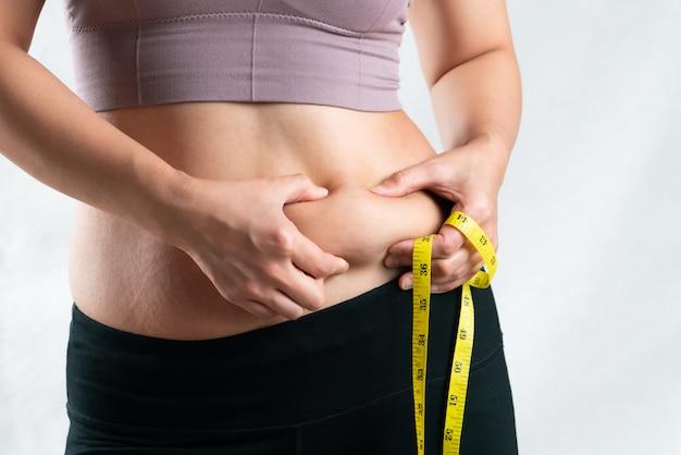 Fette frau, fetter bauch, mollige, fettleibige frauenhand, die übermäßiges bauchfett mit maßband, fraudiät-lebensstilkonzept hält Premium Fotos