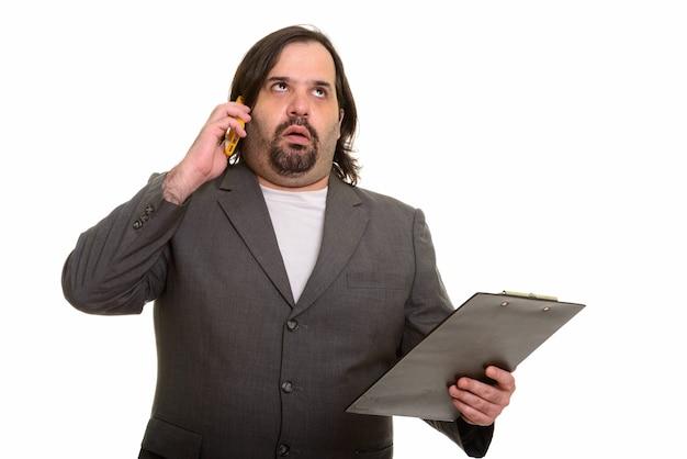 Fetter kaukasischer geschäftsmann, der genervt schaut, während er auf handy spricht und zwischenablage hält Premium Fotos