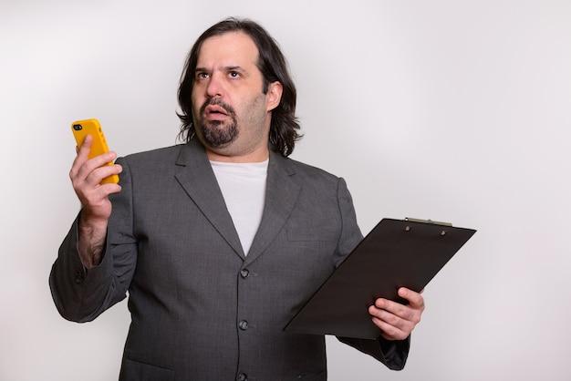 Fetter kaukasischer geschäftsmann, der genervt schaut, während er handy und zwischenablage hält Premium Fotos