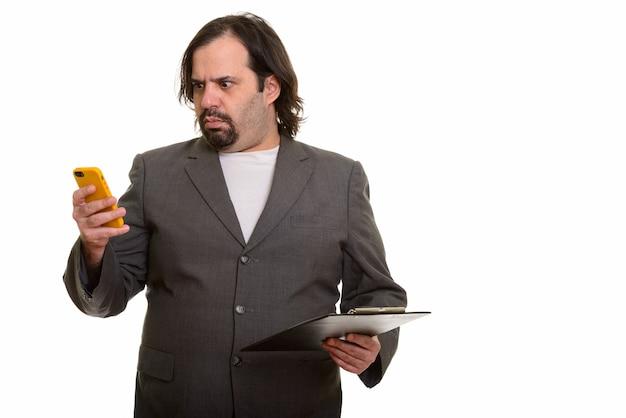 Fetter kaukasischer geschäftsmann, der gestresst schaut, während er handy und zwischenablage hält Premium Fotos