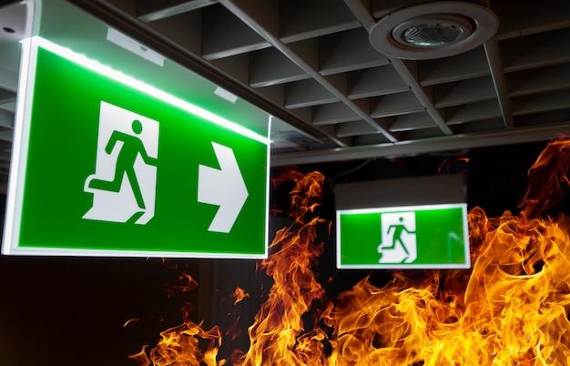 Feuer der heißen flamme und grünes notausgangzeichen hängen an der decke im büro nachts. Premium Fotos