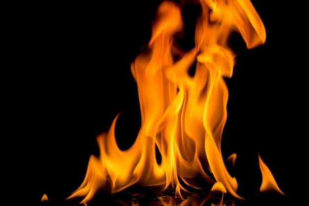 Feuerflamme auf schwarzem hintergrund. strukturierter hintergrund der flammenfeuerflamme. Premium Fotos