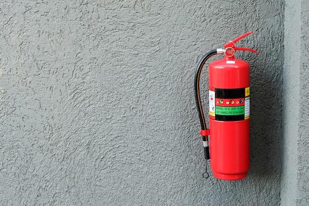 Feuerlöscher auf der grauen zementwand. Premium Fotos