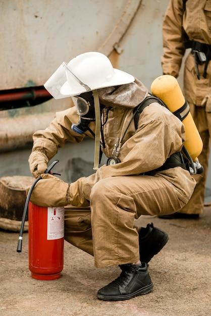 Feuerwehrmann überprüft seine ausrüstung und feuerlöscher beim training Premium Fotos