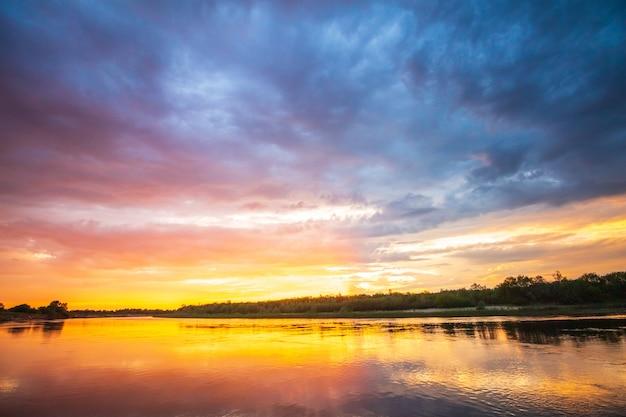 Feuriger sonnenuntergang auf dem fluss mit spiegelung im wasser Premium Fotos
