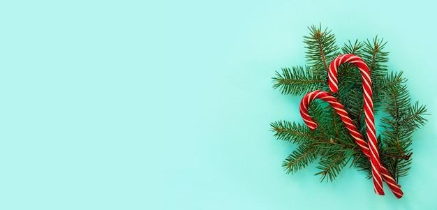 Fichtenzweige und rote bonbons auf blauem grund. flache lage, draufsicht, kopierabstand. weihnachtskonzept, feiertagspostkarte. modernes, trendiges design. banner Premium Fotos