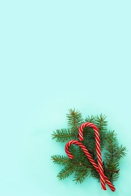 Fichtenzweige und rote bonbons auf blauem grund. flache lage, draufsicht, kopierraum, diagonale. weihnachtskonzept, feiertagspostkarte. modernes, trendiges design Premium Fotos