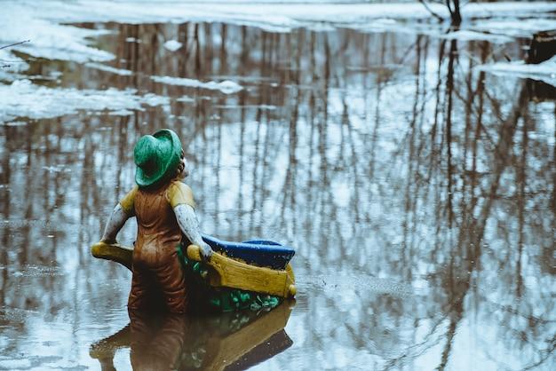 Figur in form von gnom steht mit dem rücken mit karren im wasser im frühjahr Premium Fotos
