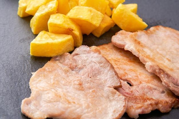 Filetsteaks mit pommes frites auf schwarzem schieferteller Premium Fotos