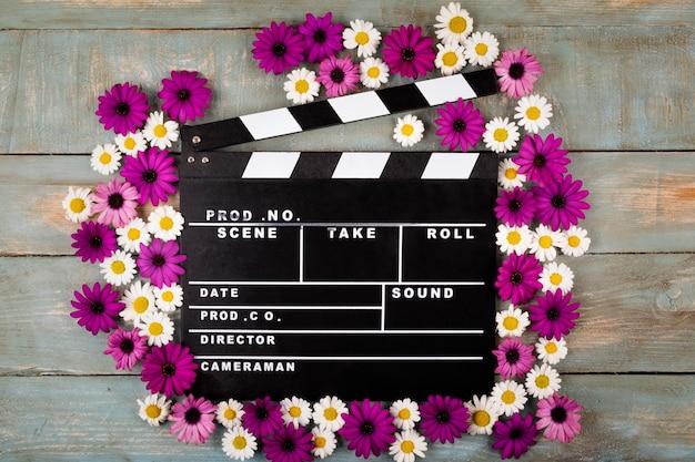 Filmklöppel mit blumen in der blauen holzoberfläche Premium Fotos